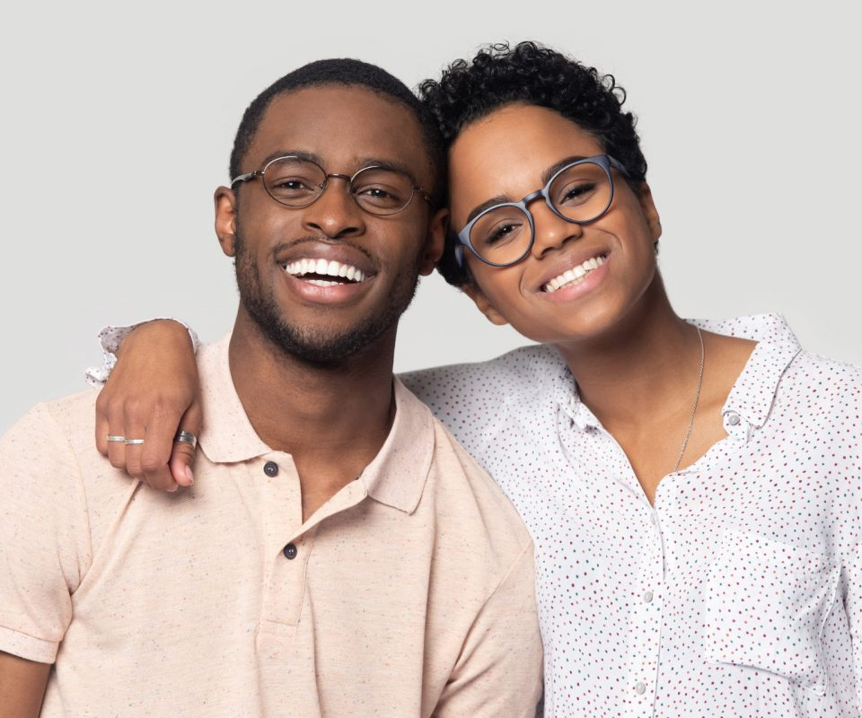 Head shot portrait African attractive married couple in glasses embracing smiling looking at camera posing isolated on grey background, love and relations, clients of photo shooting in studio concept