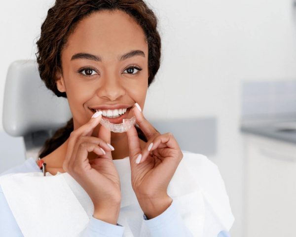 Dental Treatment Concept. Close up of young black woman holding invisible aligner, whitening tray, free space